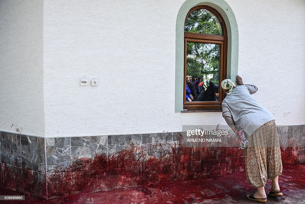 A woman looks through the church window, as the blood of ritually slaughtered sheep is seen on the ground, in the village of Babaj Bokes, during celebrations marking Saint George's Day. Saint George is the patron saint of several countries and cities. / AFP / ARMEND