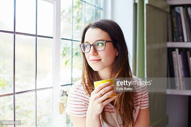 Woman looks through window thoughtfully