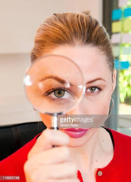 Woman looks thru magnifying glass