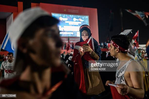 A woman looks to her mobile phone as people leave on August 7 2016 in Istanbul after a rally against a failed military coup on July 15 Hundreds of...