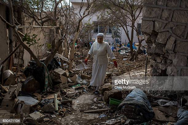 A woman looks to salvage items from the rubble at the back of a church in Qaraqosh on December 22 2016 in Mosul Iraq In recent weeks the push to...