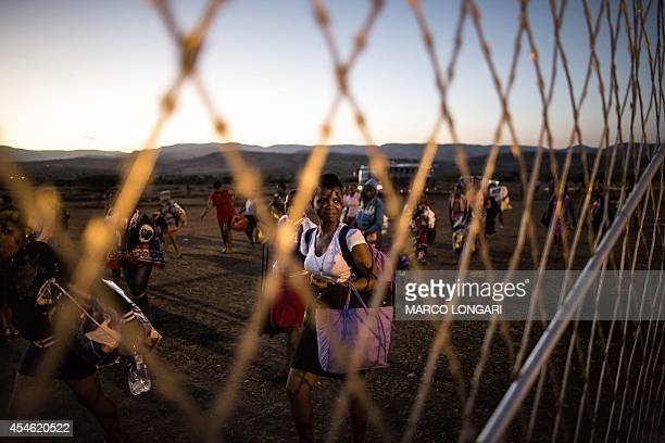 A woman looks towards the fence as hundreds of South African maidens arrive on September 4 2014 at the eNyokeni Royal Palace in Nongoma in the...