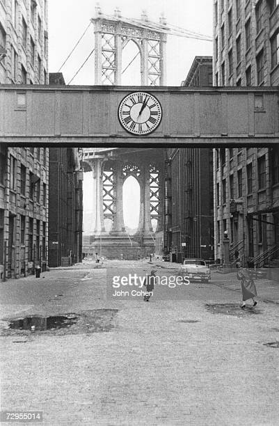 A woman looks towards the Manhattan Bridge as a young boy runs in the street under a skyway on which is mounted a clock Washington Street between...