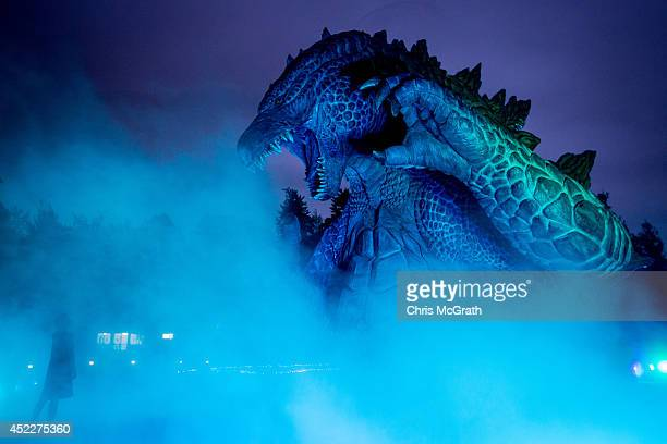 A woman looks up at a 66 meter replica Godzilla as it is lit up during a press preview at Tokyo Midtown on July 17 2014 in Tokyo Japan The 'MIDTOWN...