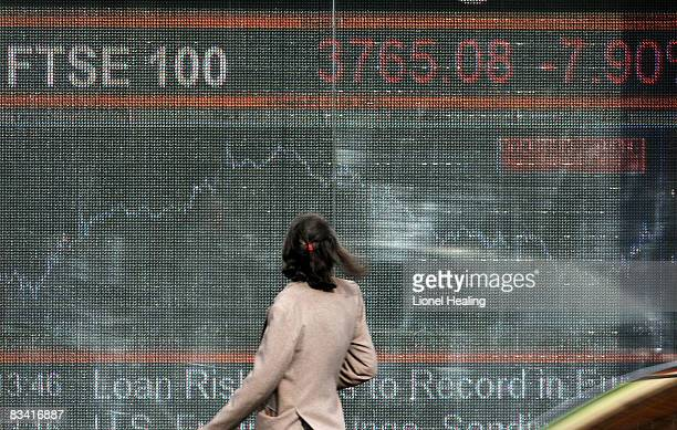 A woman looks up towards an electronic sign showing the FTSE 100 share index on October 24 2008 on London England The FTSE fell by more than 300...