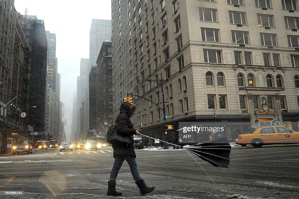 A woman loses her umbrella in New York on February 8, 2013 during a storm affecting the northeast US. The storm was forecast to bring the heaviest snow to the densely-populated northeast corridor so far this winter, threatening power and transport links for tens of millions of people and the major cities of Boston and New York. New York and other regional airports saw more than 4,500 cancellations ahead of what the National Weather Service called 'a major winter storm with blizzard conditions' along most of the region's coastline. AFP PHOTO / MEHDI TAAMALLAH