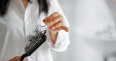 woman losing hair on hairbrush in hand on bathroom background, soft focus