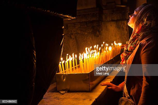JERUSALEM ISRAEL PALESTINE JERUSALEM ISRAEL A woman lost in thoughts and praying Jesus Christ at the holy Sepulchre church in Jerusalem the holiest...