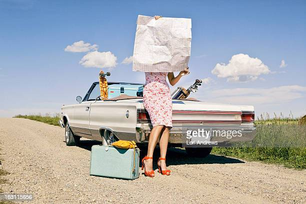 Woman lost on side of road holding a map
