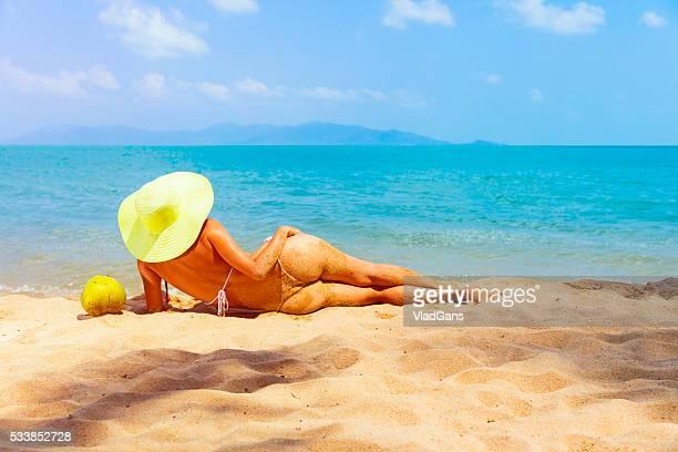Mujer acostada en playa tropical
