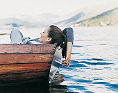 Woman Lying Back in a Rowing Boat and Dipping her Hand in the Water