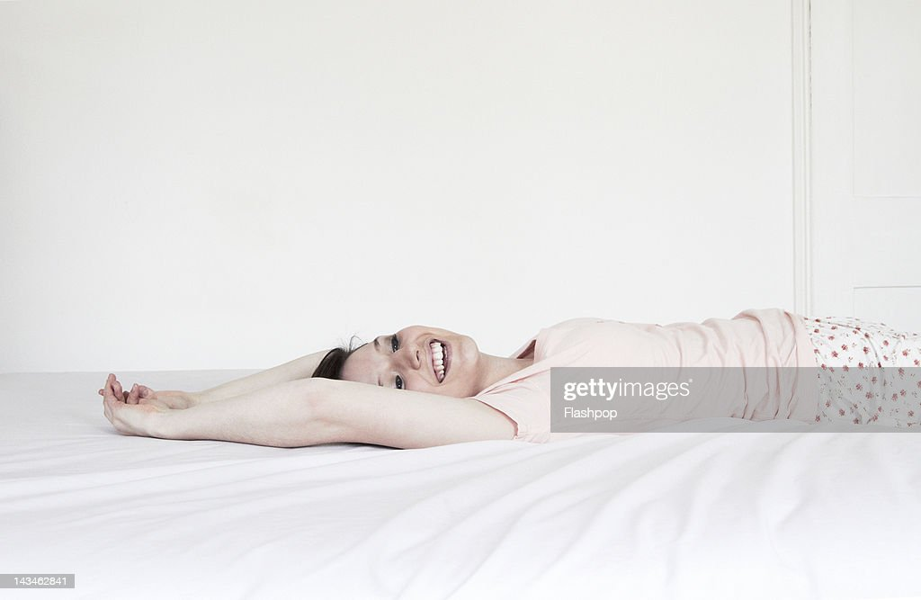 Woman lying back relaxing on bed : Stock Photo