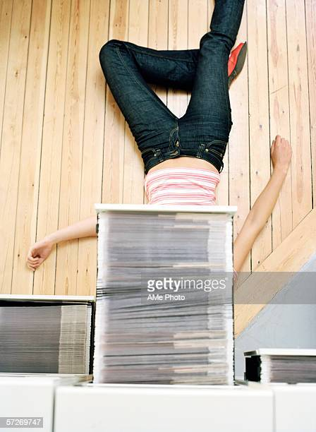 A woman lying beneath a pulled out drawer in a filing cabinet.