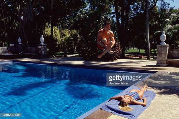 Woman lying beside swimming pool, man diving in above her