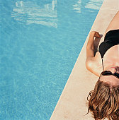 Woman lying by side of pool