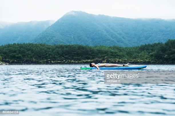 Woman lying down on paddling board