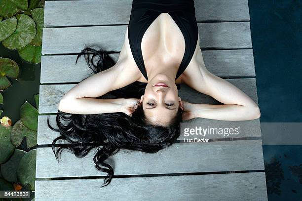 Woman lying down on wooden deck