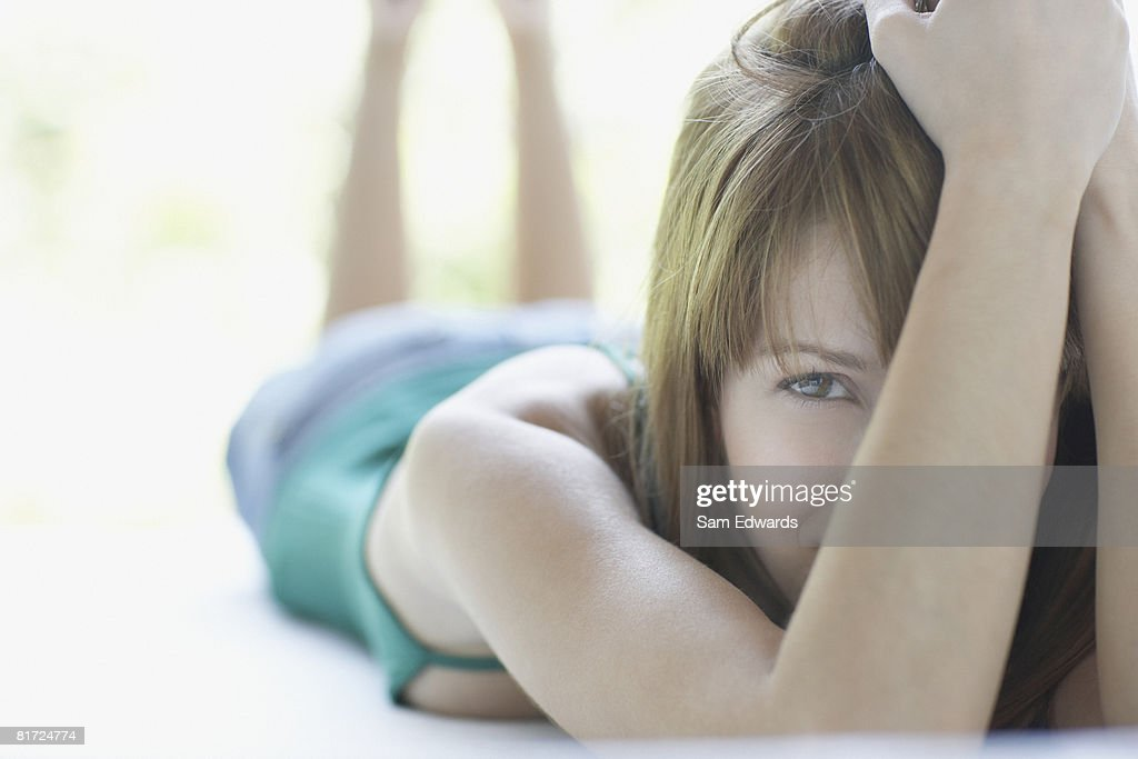 Woman lying down relaxing and looking at camera : Stock Photo