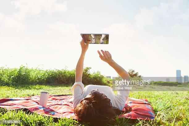 Woman lying down using digital tablet