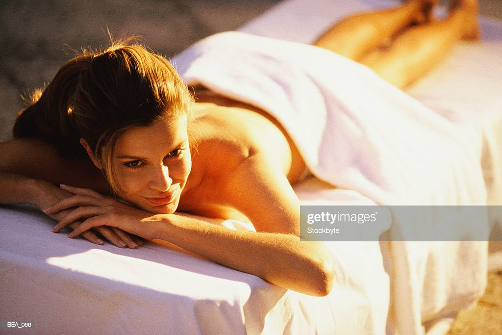 ... Woman lying face down on massage table, with towel draped over back