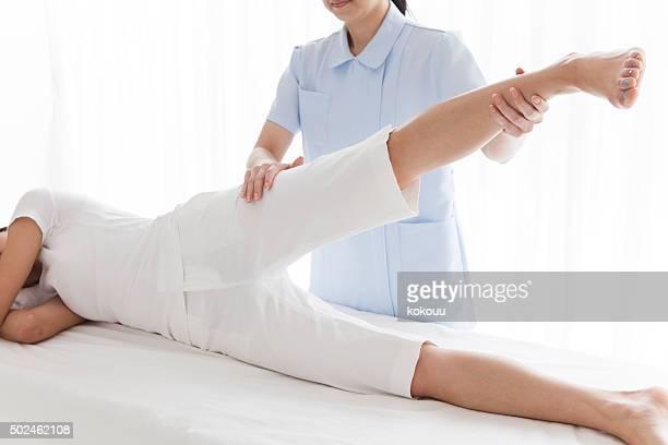 女性の体をした理学療法士による調べる彼女の足