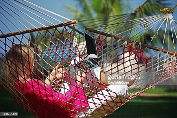 Woman lying in a hammock and working with a notebook on January 12 2010 in Varkala near Trivandrum Kerala India