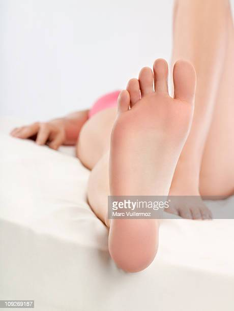 Woman lying in bed, close-up of foot sole