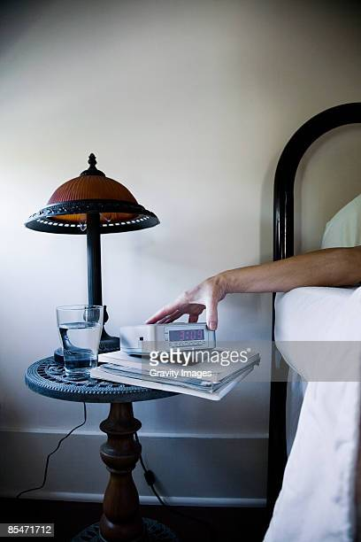 Woman lying in bed, holding alarm clock