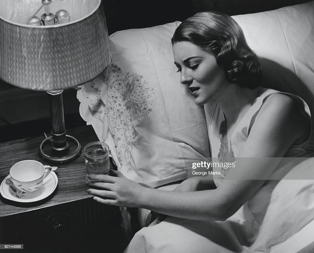 Woman lying in bed, reaching for glass of water, (B&W), elevated view : Stock Photo