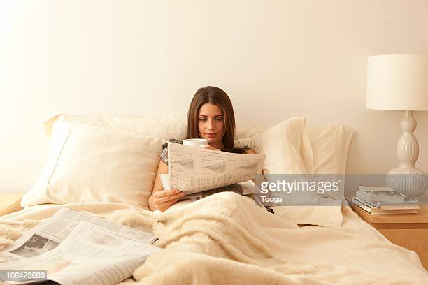Woman lying in bed reading newspaper