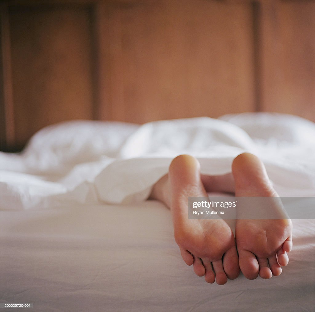 Woman lying in bed under sheet (focus on feet) : Stock Photo