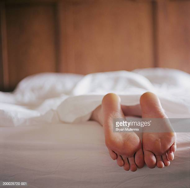 Woman lying in bed under sheet (focus on feet)