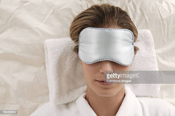 Woman lying in bed with satin eye mask