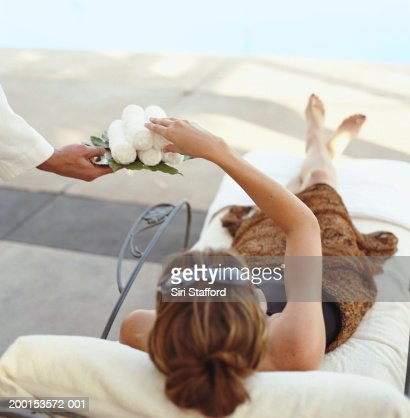 Woman lying in chair by pool, taking washcloth form hotel attendant