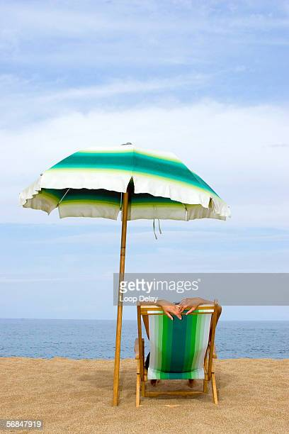 Woman relaxing on lounge chair under umbrella, rear view
