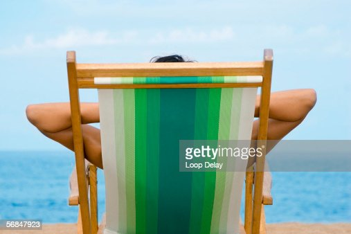 Woman relaxing on lounge chair, rear view, close-up