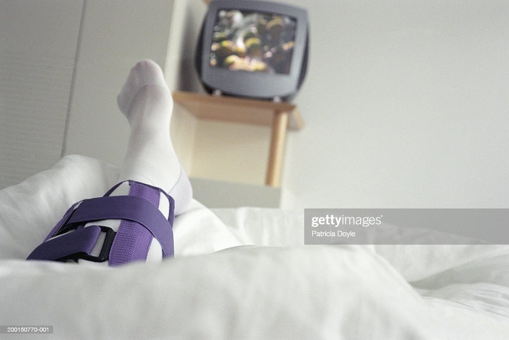 Woman lying in hospital bed, leg in cast (focus on leg) : Stock Photo