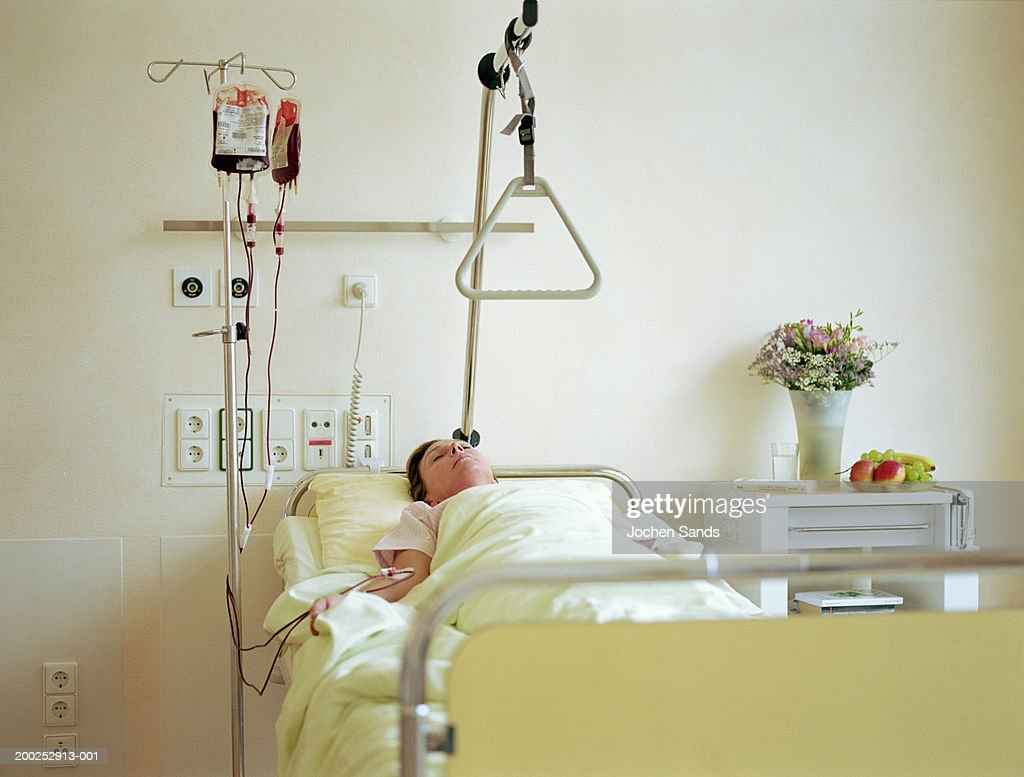 Woman lying in hospital bed with IV drip filled with blood : Stock Photo