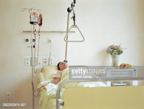 Mulher deitada na cama do hospital com um gotejamento intravenoso cheia com sangue