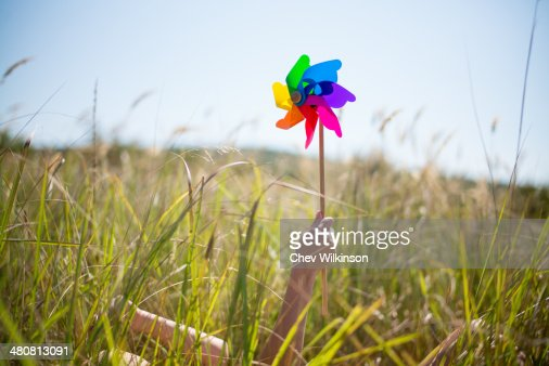 Woman lying in long grass holding windmill