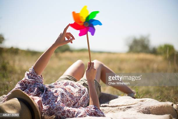 Woman lying in on back holding windmill