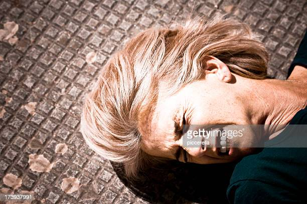 A woman lying in pain on a tile floor