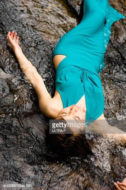Woman lying in river