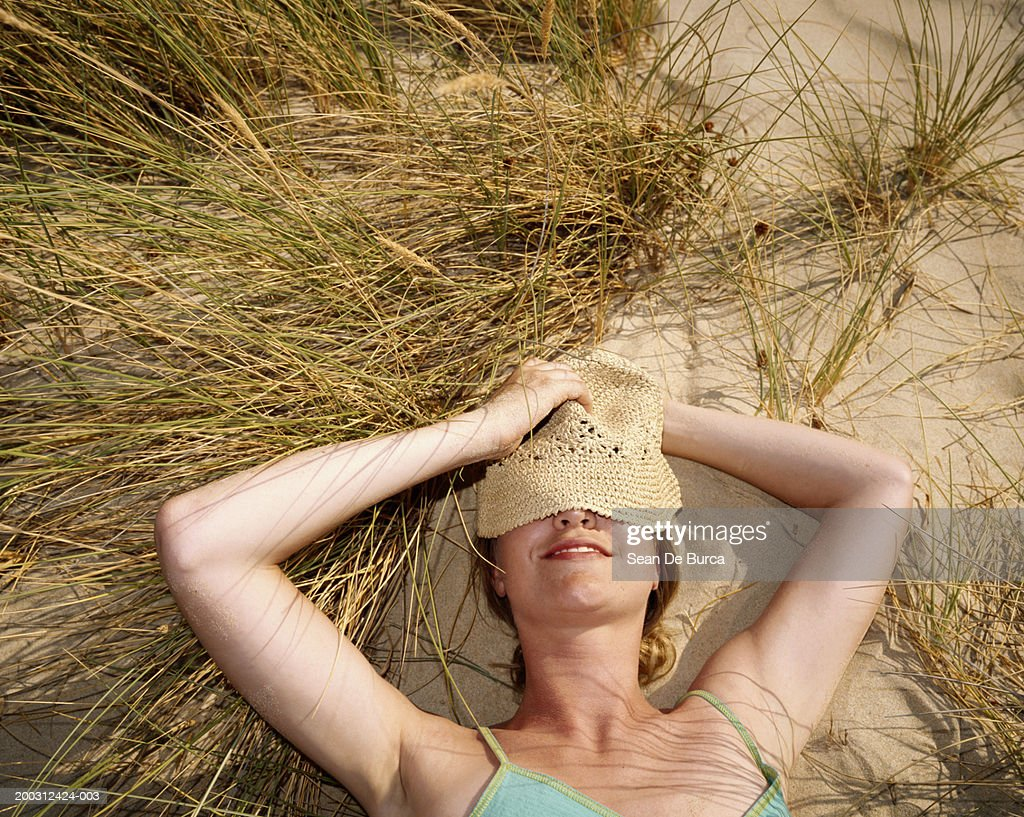 Woman lying in sea grass, hat covering eyes, elevated view : Stock Photo
