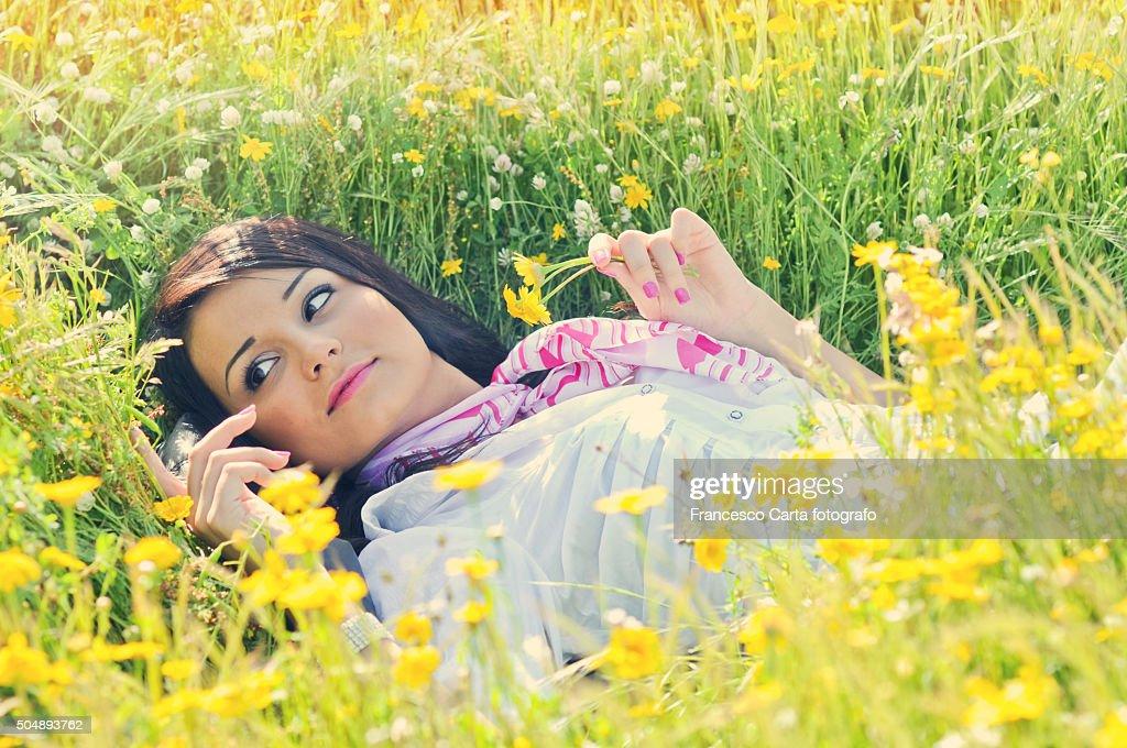 Woman lying in the field of daisy