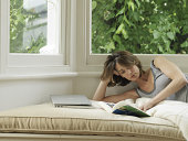 Woman lying in window alcove reading book