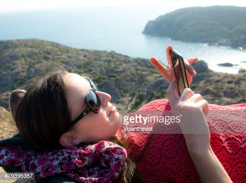 Woman lying near the sea using the mobile phone : Stock Photo