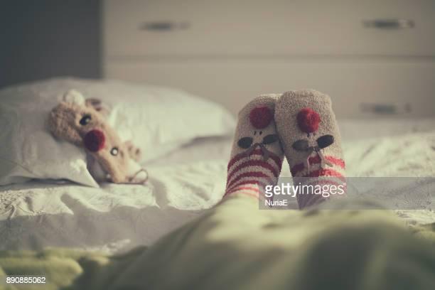 Woman lying on a bed wearing Christmas reindeer socks