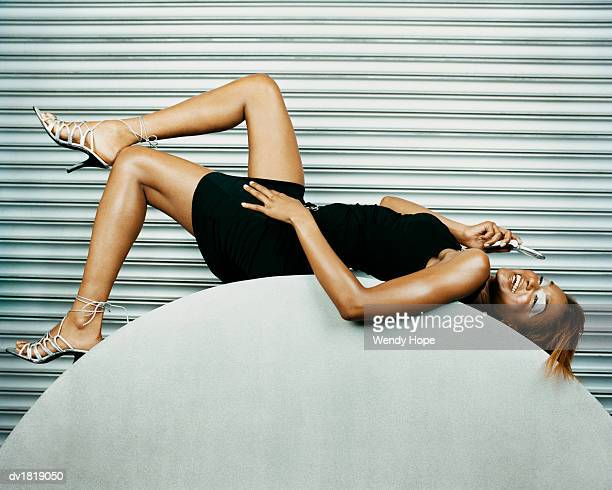 Woman Lying on a Curved Object Using a Mobile Phone