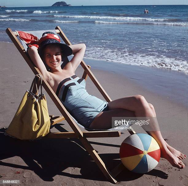 woman lying on a deck chair at the beach 1950s